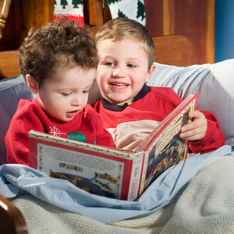 Two brothers reading a christmas book in bed